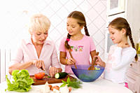 Grandmother and granddaughters preparing food in kitchen