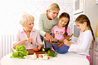 Multi-generational family preparing food in kitchen