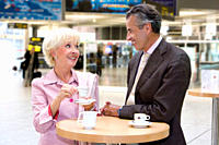 Senior couple having coffee in transportation center