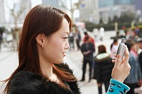 Side profile of a young woman looking at a mobile phone