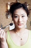 Portrait of a young woman applying make-up on her face