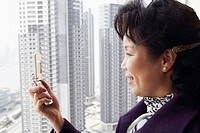 Side profile of a businesswoman looking at a mobile phone smiling