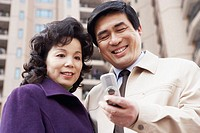 Low angle view of a mature couple looking at a mobile phone smiling