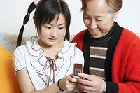 Close-up of a young woman with her grandmother holding a mobile phone