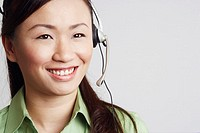 Close-up of a female customer service representative looking away and smiling