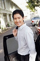Portrait of a businessman standing near a car and smiling
