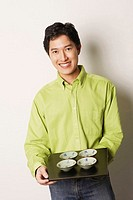 Portrait of a young man holding a tray of bowls smiling