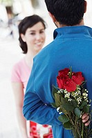 Young man hiding a bunch of roses behind his back with a young woman in front of him