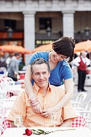 Young woman with her arm around a mature man at a sidewalk cafe