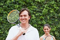 Mid adult man and a young woman holding tennis rackets and smiling