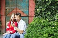 Mid adult man and a teenage girl looking at a mobile phone (thumbnail)