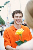 Close-up of a young man holding a flower