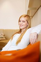 Side profile of a young woman sitting on a couch