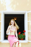 Portrait of a young woman holding an ice-cream cone and sitting in a window