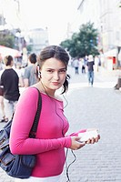Portrait of a young woman holding an MP3 player