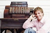 Portrait of a young man talking on a mobile phone near a typewriter