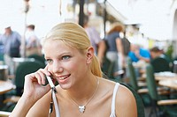Close-up of a young woman talking on a mobile phone in a restaurant
