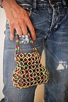 Mid section view of a gay man holding a hand bag