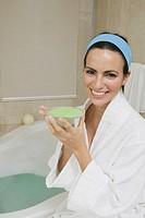 Portrait of a young woman sitting near a bathtub holding a dish of bath crystals