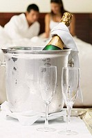 Close-up of a champagne bottle in an ice bucket with two champagne flutes