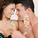 Close-up of a young man and a teenage girl holding champagne flutes
