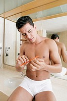 Close-up of a young man filing his nails in the bathroom