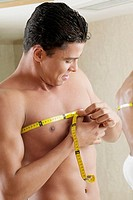 Close-up of a young man measuring his chest with a tape measure