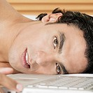 Portrait of a young man lying near a laptop