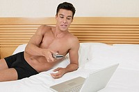 Young man lying on the bed using a remote control with a laptop in front of him