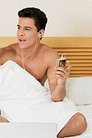 Young man sitting on the bed and listening to an MP3 player