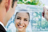 Close-up of a groom lifting his bride's veil