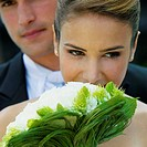 Close-up of a bride holding a bouquet of flowers with her groom in the background