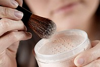Close-up of a woman's hand holding a pot of face powder and a make-up brush