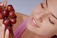 Close-up of a young woman holding a bunch of red grapes