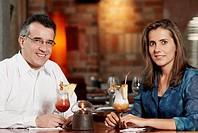 Portrait of a mid adult couple sitting in a restaurant with two glasses of pina colada
