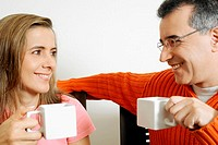 Close-up of a mid adult couple holding two cups of coffee