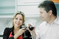 Close-up of a mid adult woman and a mature man toasting glasses of wine and smiling
