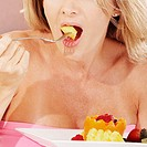 Close-up of a young woman eating fruit salad with a fork