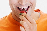 Close-up of a young man eating a strawberry
