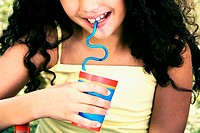 Close-up of a girl holding a disposable cup and drinking with a straw