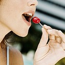 Close-up of a young woman eating a cherry