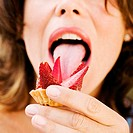 Close-up of a young woman licking a strawberry tart