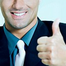 Close-up of a businessman showing thumbs up sign and smiling