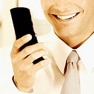 Close-up of a businessman holding a mobile phone and smiling