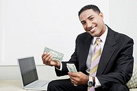 Portrait of a businessman sitting beside a laptop and counting paper currency