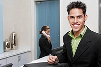 Portrait of a businessman standing at a hotel reception with a receptionist talking on the telephone behind him