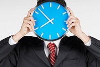 Close-up of a businessman holding a clock in front of his face