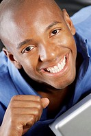 Portrait of a young man smiling in front of a laptop