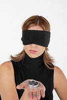 Close-up of a businesswoman showing a compass with her eyes blindfolded