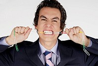 Portrait of a businessman biting a chain of paper clips
